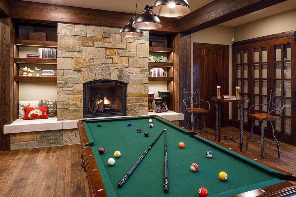 Rec room with pool table and adjacent fireplace featuring natural stone with shades of tan, brown, and gold.