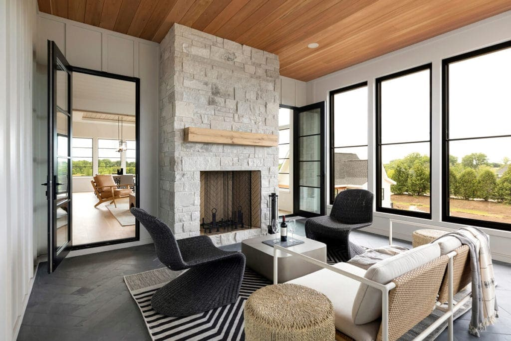 modern sunroom featuring a white stone fireplace